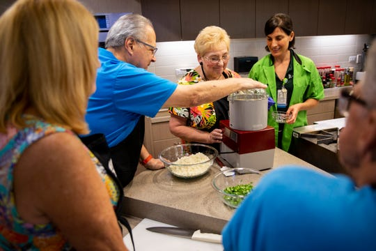 Dietitian Aikaterina Galeos, right, shows Tom and Sue Kerekes how to use a food processor to make cauliflower rice during a cooking class, part of the FARMacy RX Cardiac Cooking Series at Lee Health Coconut Point in Estero on Friday, March 15, 2019. The class is free to patients in cardiac rehab, who are able to bring a spouse, friend or caregiver with them.