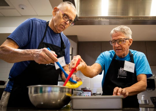 Roger Hatch, left, and Michael Domina glaze pineapple during a cooking class, part of the FARMacy RX Cardiac Cooking Series at Lee Health Coconut Point in Estero on Friday, March 15, 2019.