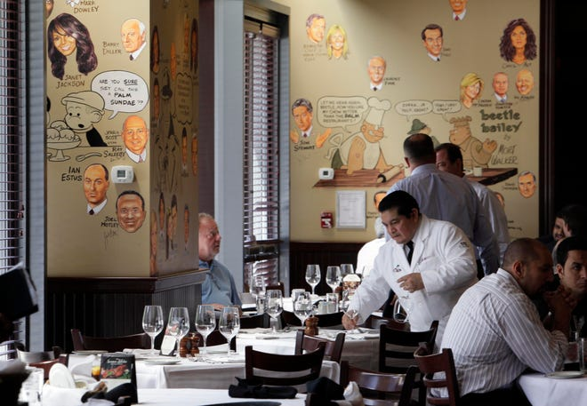 In this file photo from 2011 photo, a waiter resets a table at The Palm restaurant in New York's Tribeca neighborhood. After opening its doors in 1926, The Palm restaurant soon became a gathering place for bold-faced names.
