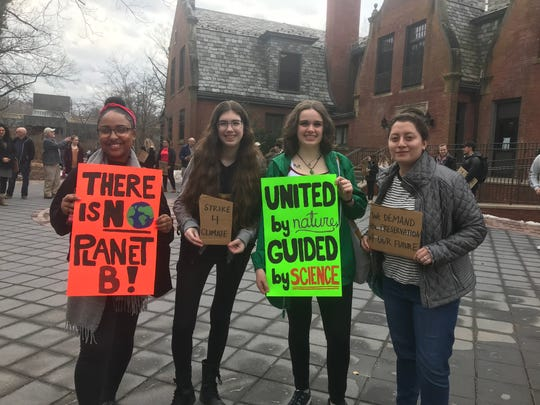 Ramapo College students hold a silent protest for climate change awareness outside of the college's Birch Mansion.