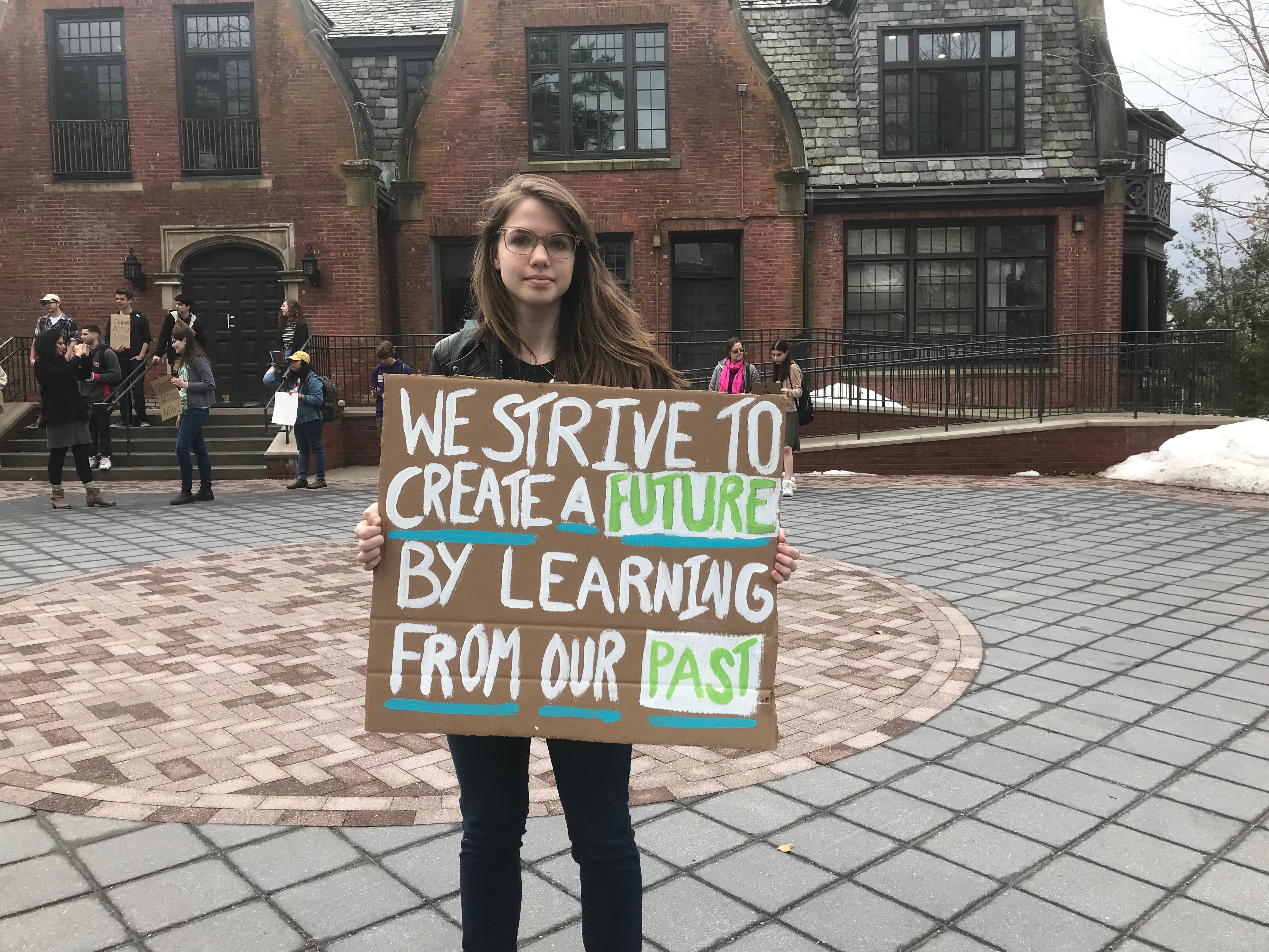 Ramapo College senior Angelica Pasquali holds a sign at the school's Birch Mansion promoting climate change awareness.