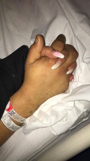 Marie Gamboa holds Angel Flores' hand in the intensive care unit at MountainView Hospital Regional Medical Center. Flores, her boyfriend, was shot in the chest after confronting a man who allegedly stole Gamboa's wallet at a barber shop Monday, March 4, 2019.