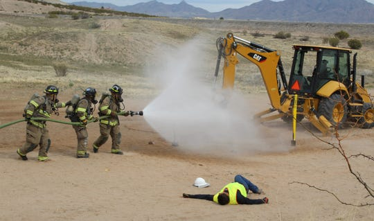 The Las Cruces Fire Department uses a fire hose recently to spray water that temporarily pushes the gas away so they can rescue a fallen worker. Thankfully, this was only a training hosted by Las Cruces Utilities to allow different local and state agencies practice their roles during a gas emergency.