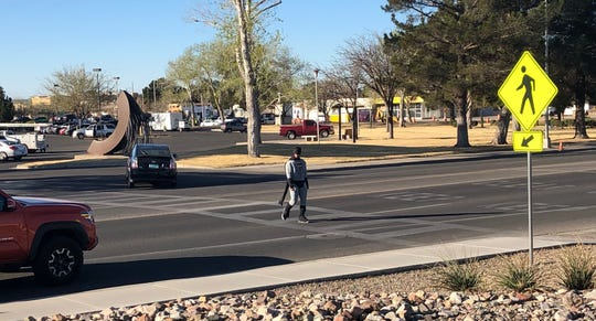 A costumed police officer walks across Picacho Avenue near the city police and fire stations as part of a traffic enforcement operation on Thursday, March 14, 2019. Las Cruces police ticketed drivers who failed to yield.