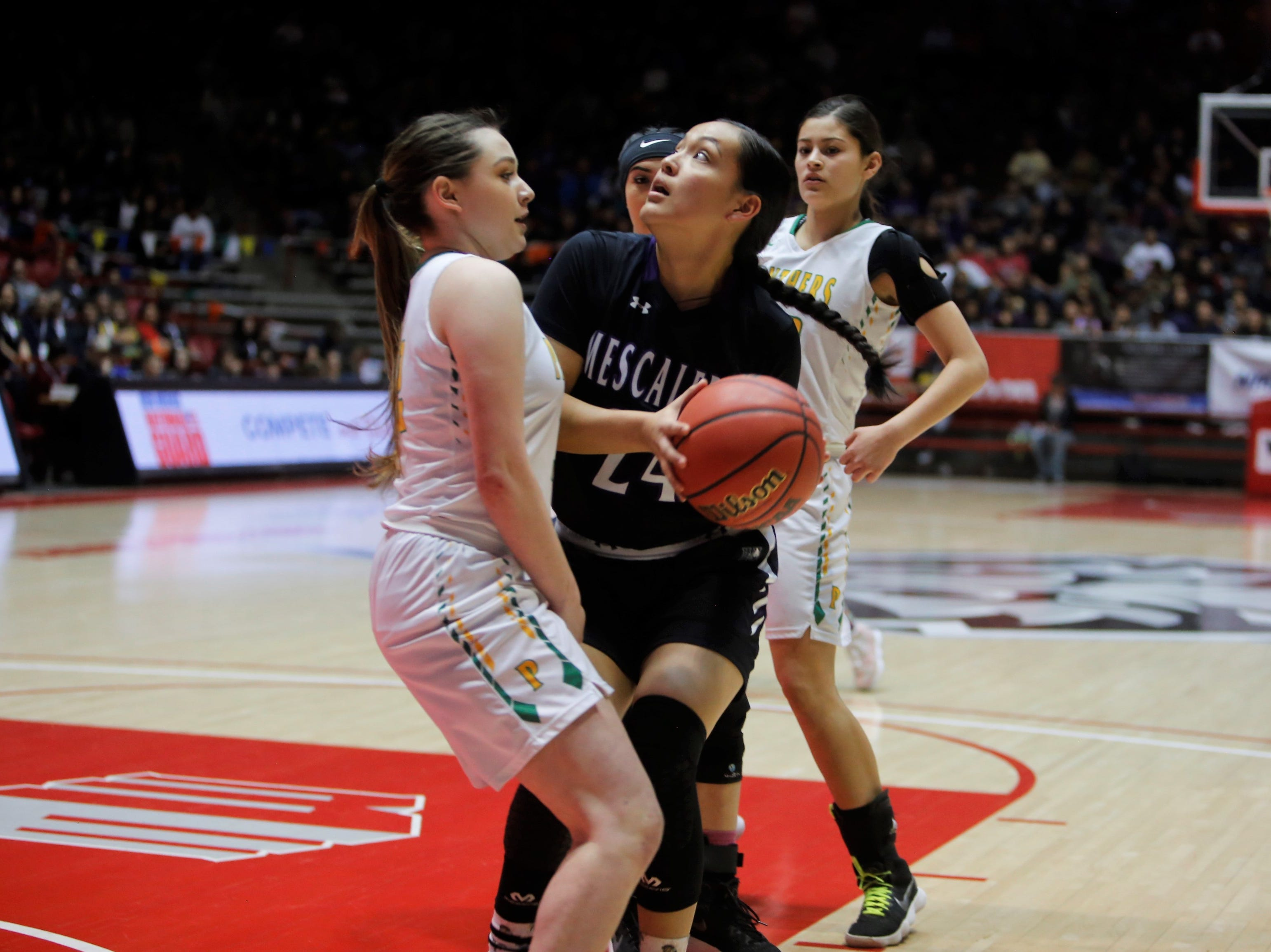 Mescalero Apache's Samantha Kazhe makes contact with Pecos's Cassaundra Muller going to the basket during Friday's 2A state championship game at Dreamstyle Arena in Albuquerque.