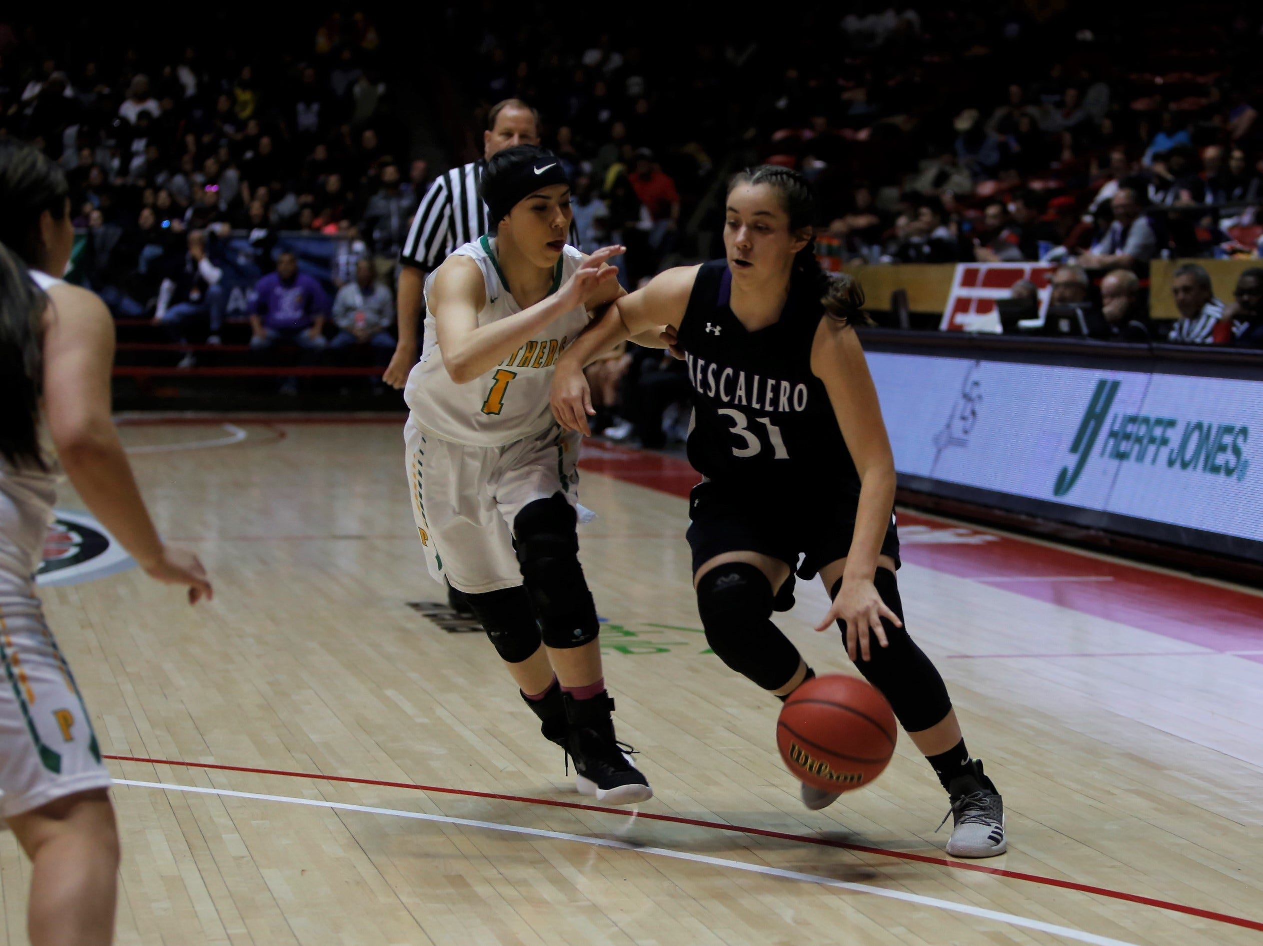 Mescalero Apache's Fallon Velasquez drives toward the basket against Pecos's Trinity Herrera during Friday's 2A state championship game at Dreamstyle Arena in Albuquerque.