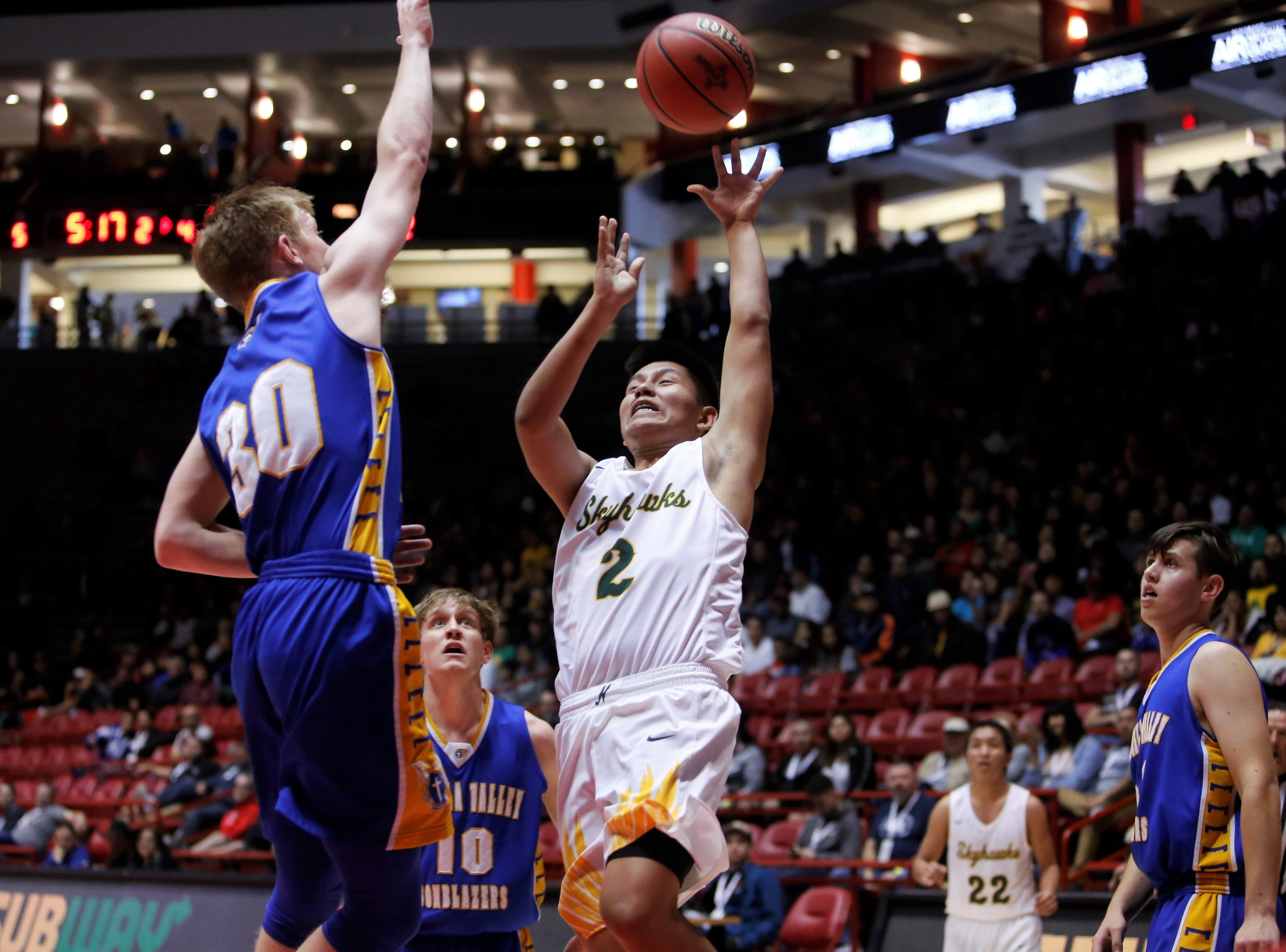Newcomb's Deion Johnhat puts up a shot against Mesilla Valley's Nolan Nunley (30) during Friday's 2A state semifinals at Dreamstyle Arena in Albuquerque.