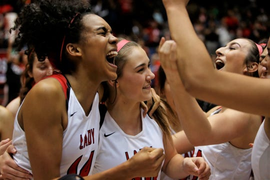 Robertson's Alianza Darley (14), Shayla Hillis (20) and Tessa Ortiz (24) celebrate winning Friday's 3A state championship game at Dreamstyle Arena in Albuquerque. Robertson defeated Santa Fe Indian, 62-46.