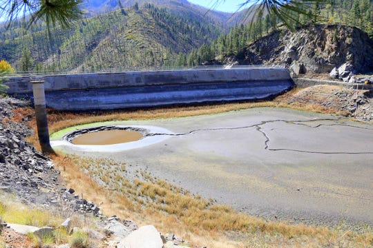 Material at the bottom of Bonito Lake is being dredged, exposing the dam.
