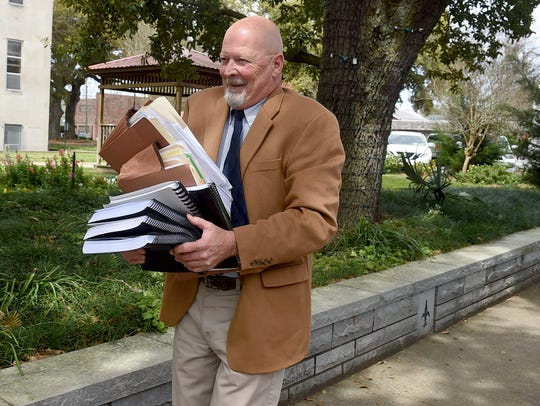 Frank Olivier III carries court files in connection with his defense of former Opelousas Mayor Reggie Tatum. Olivier was discharged as Tatum's attorney earlier this week.