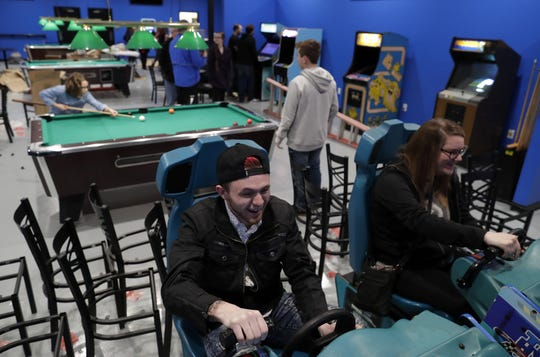 Nikk Highman, left, of Oshkosh and Haley Arndt of De Pere play the Hydro Thunder arcade game Thursday, March 14, 2019, at Pixels Arcade & Sports Bar in Oshkosh, Wis.