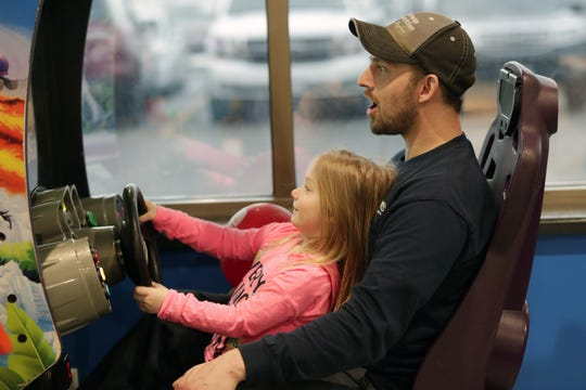 Travis Erdmann and his daughter, Reese, 4, enjoy playing the Crusing Exotica arcade game Thursday, March 14, 2019, at Pixels Arcade & Sports Bar in Oshkosh, Wis. The two are from Omro.