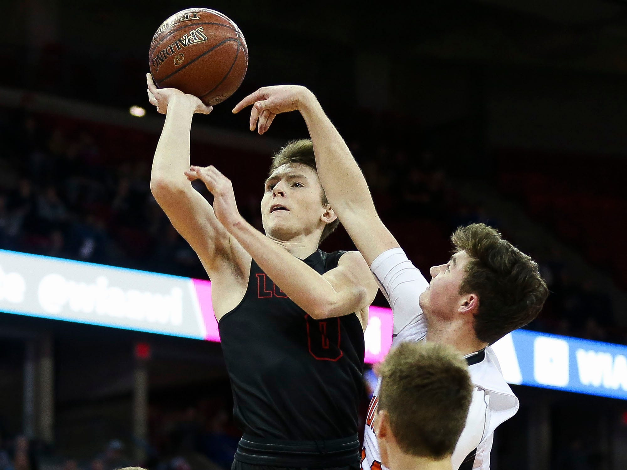 Lourdes Academy's Hayden Jones (0) charges Osseo-Fairchild High School's Logan Mulhern (21) on his way to the basket in a Division 4 boys basketball state semifinal on Thursday, March 14, 2019, at the Kohl Center in Madison, Wis. Jones hit a shot with 1.5 seconds remaining in the game to give Lourdes Academy a 70-68 victory.