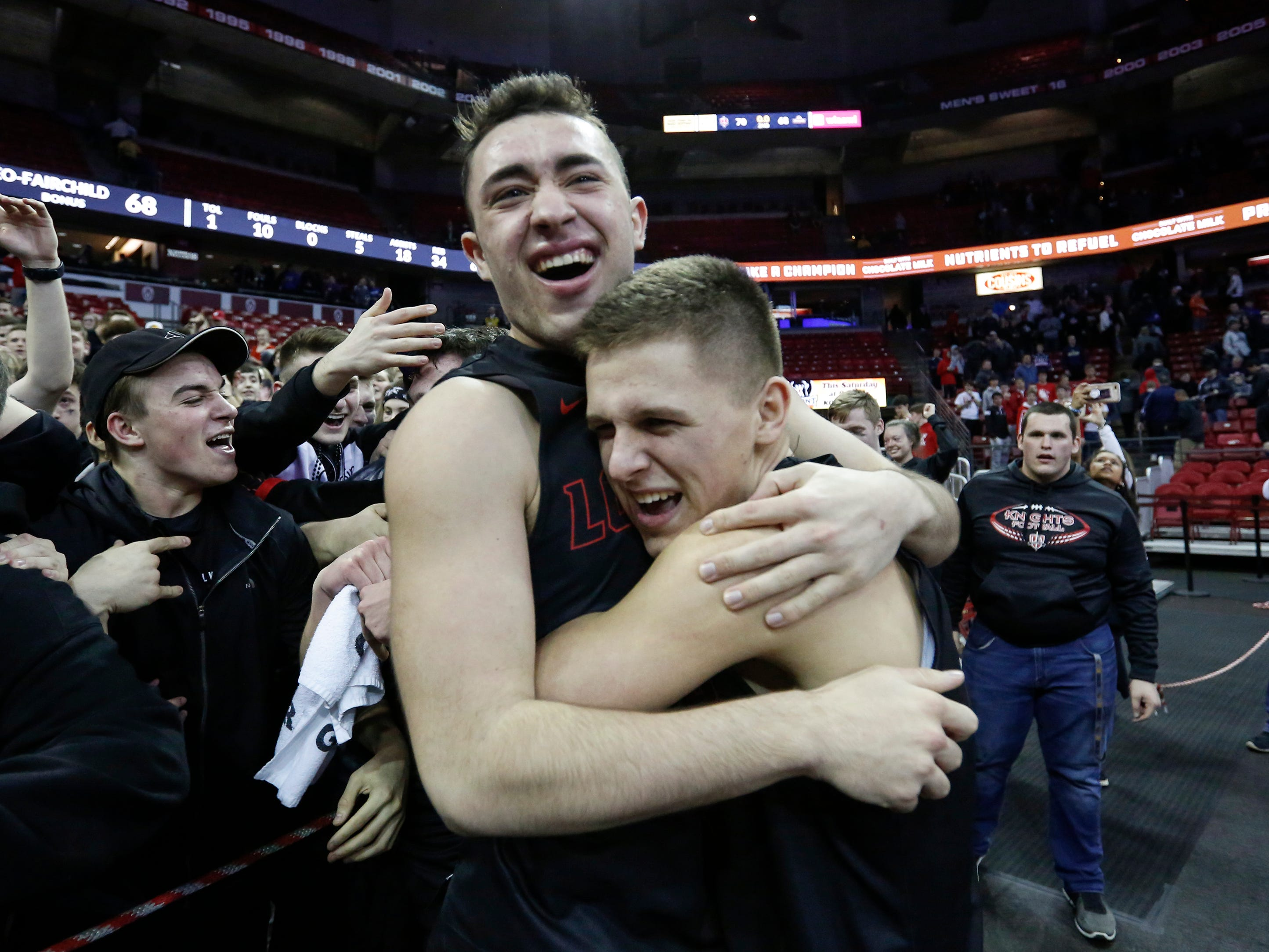 Lourdes Academy's Benny Huizenga, left, embraces teammate Caden Chier after defeating Osseo-Fairchild High School in their WIAA Division 4 boys basketball state semifinal at the Kohl Center Thursday, March 14, 2019, in Madison, Wis. Lourdes Academy defeated Osseo-Fairchild 70-68 to advance to the Division 4 championship game.
