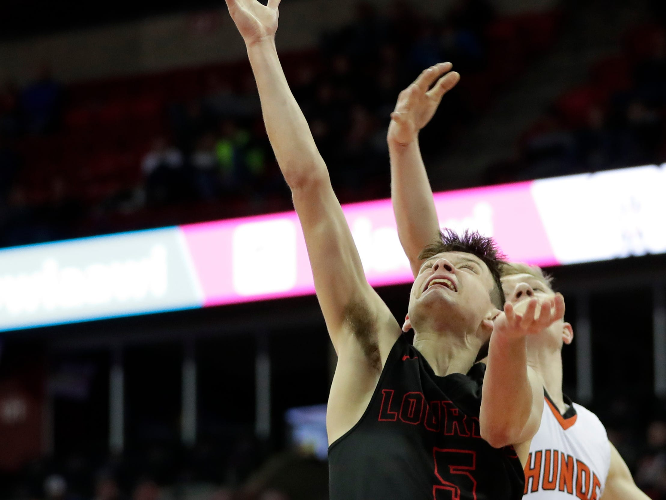Lourdes Academy's Jack McKellips (5) shoots a layup against Osseo-Fairchild High School's Alex Watenphul (12) during their WIAA Division 4 boys basketball state semifinal at the Kohl Center Thursday, March 14, 2019, in Madison, Wis.