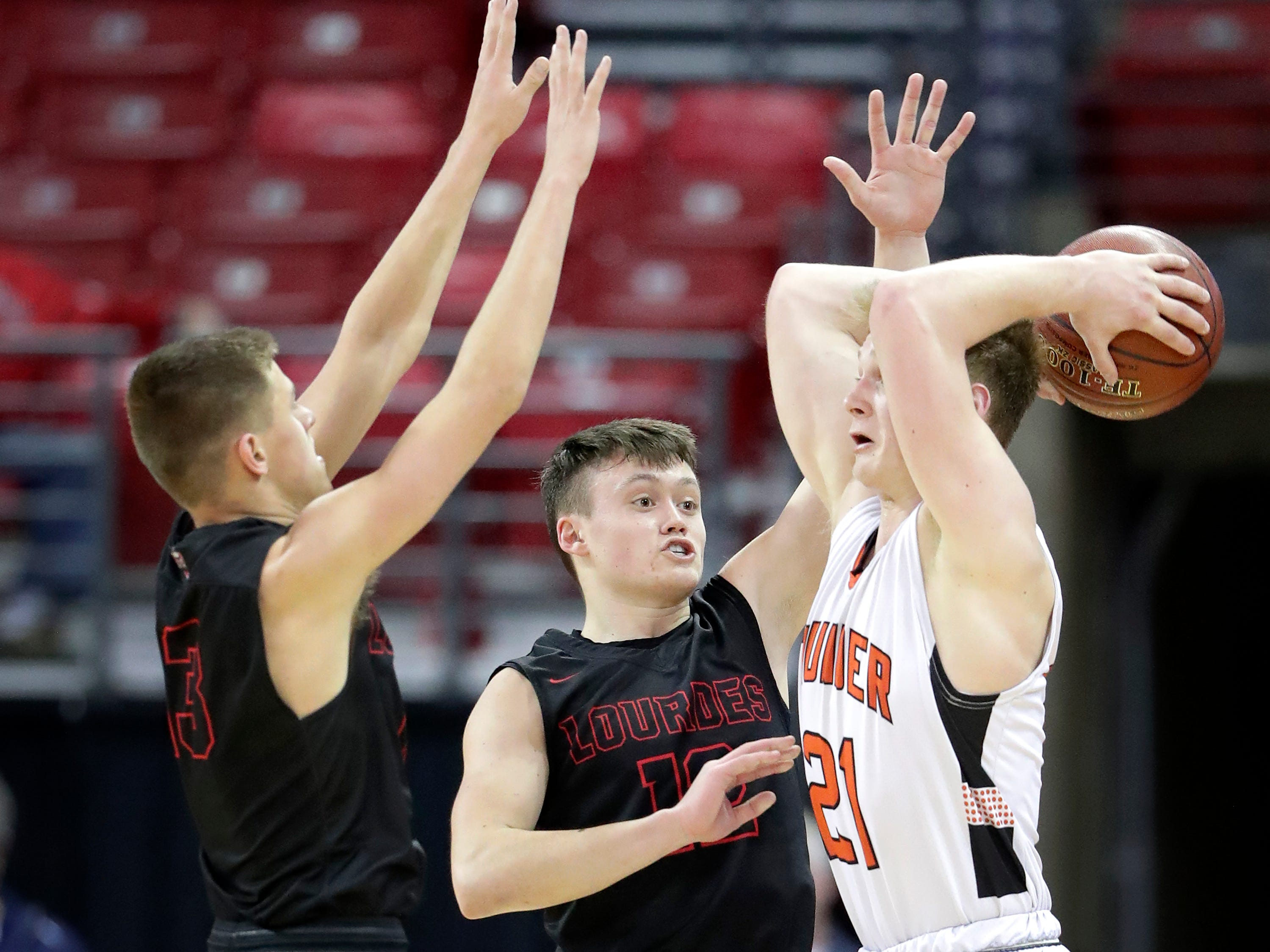 Lourdes Academy's #13 Caden Chier and #12 Joshua Bauer battle against Osseo-Fairchild High School's #21 Logan Mulherm during their WIAA Division 4 boys basketball state semifinal on Thursday, March 14, 2019, at the Kohl Center in Madison, Wis.