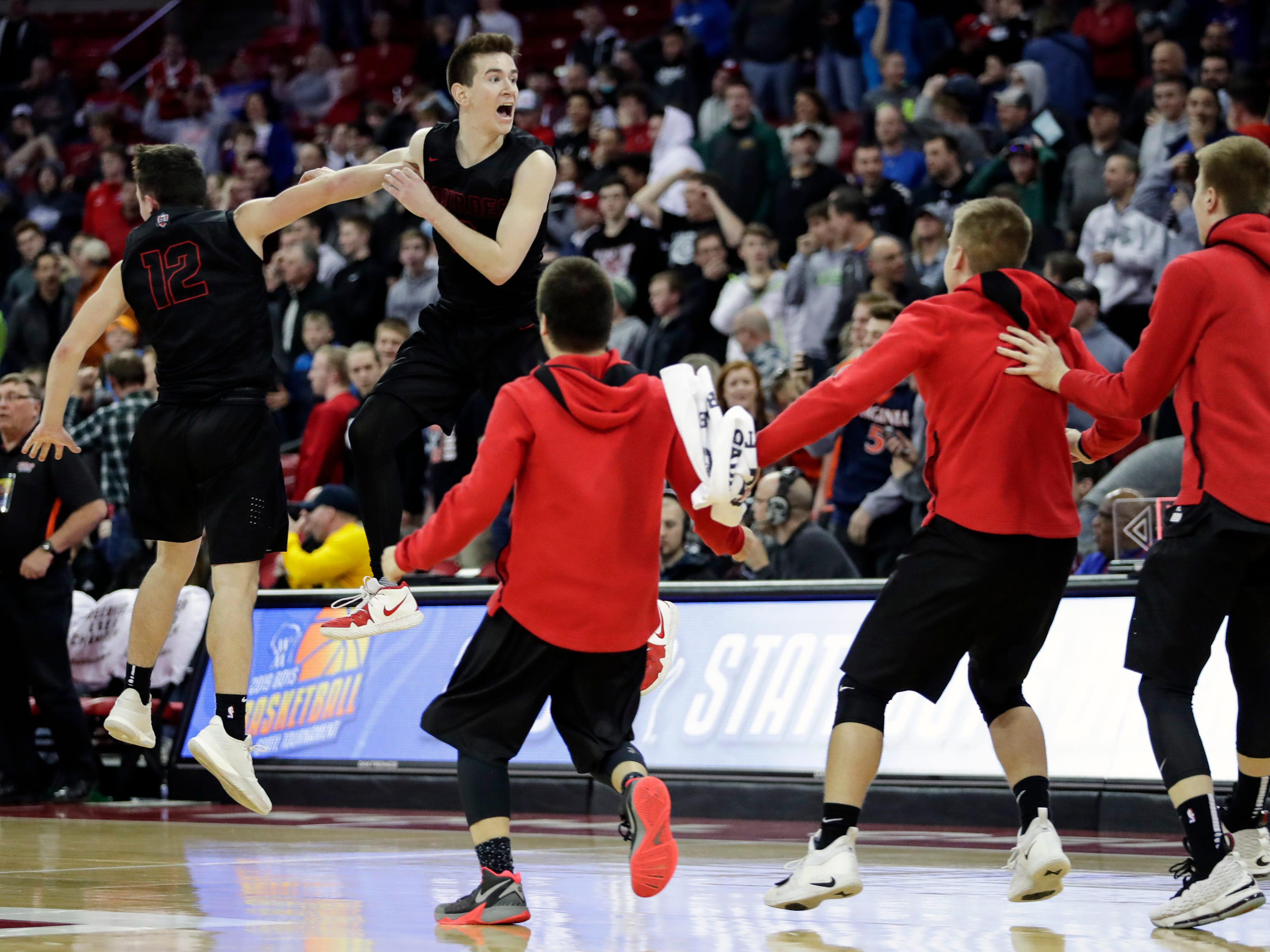 Lourdes Academy's Joshua Bauer (12) and Henry Noone (2) react after defeating Osseo-Fairchild High School in their WIAA Division 4 boys basketball state semifinal at the Kohl Center Thursday, March 14, 2019, in Madison, Wis.
