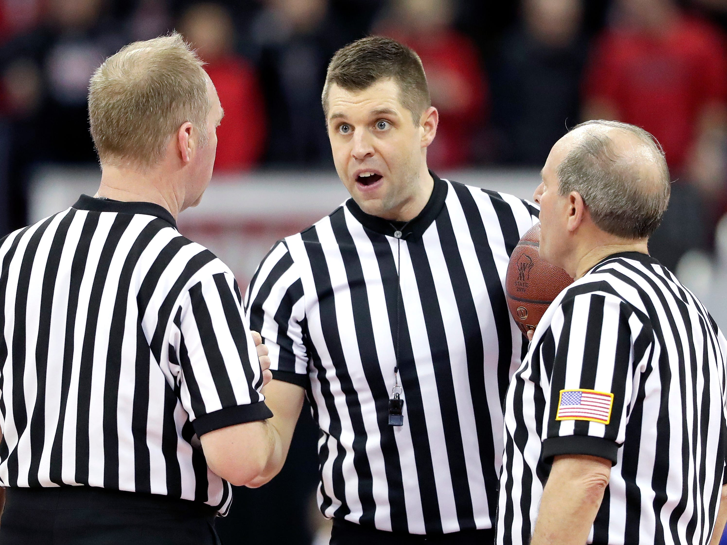 Referees discuss during their WIAA Division 4 boys basketball state semifinal on Thursday, March 14, 2019, at the Kohl Center in Madison, Wis. Lourdes defeated Osseo-Fairchild 70-68.