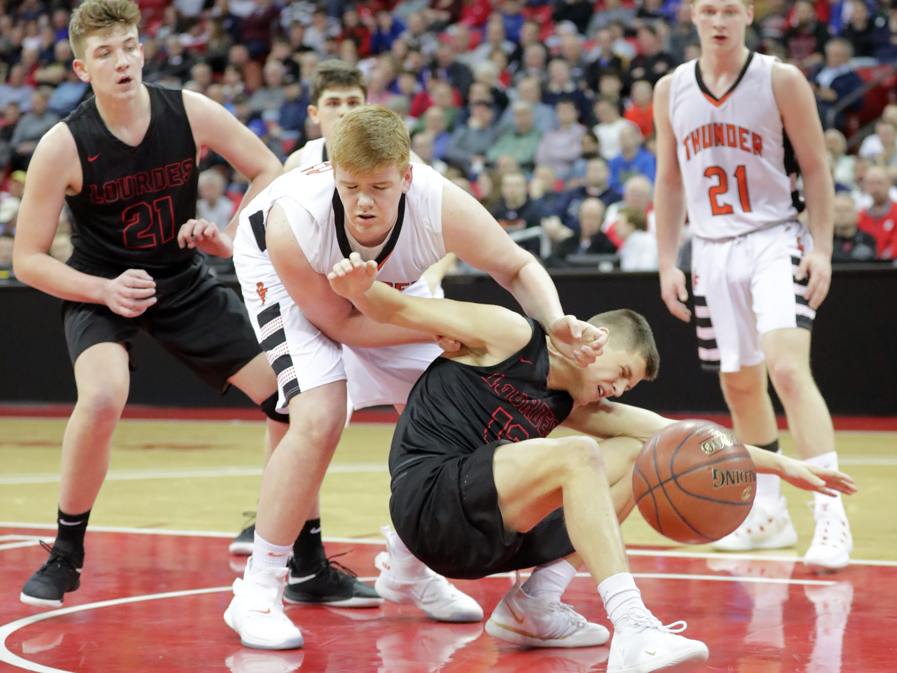 Lourdes Academy's #13 Caden Chier battle against Osseo-Fairchild High School's #52 Cory Myhers during their WIAA Division 4 boys basketball state semifinal on Thursday, March 14, 2019, at the Kohl Center in Madison, Wis.