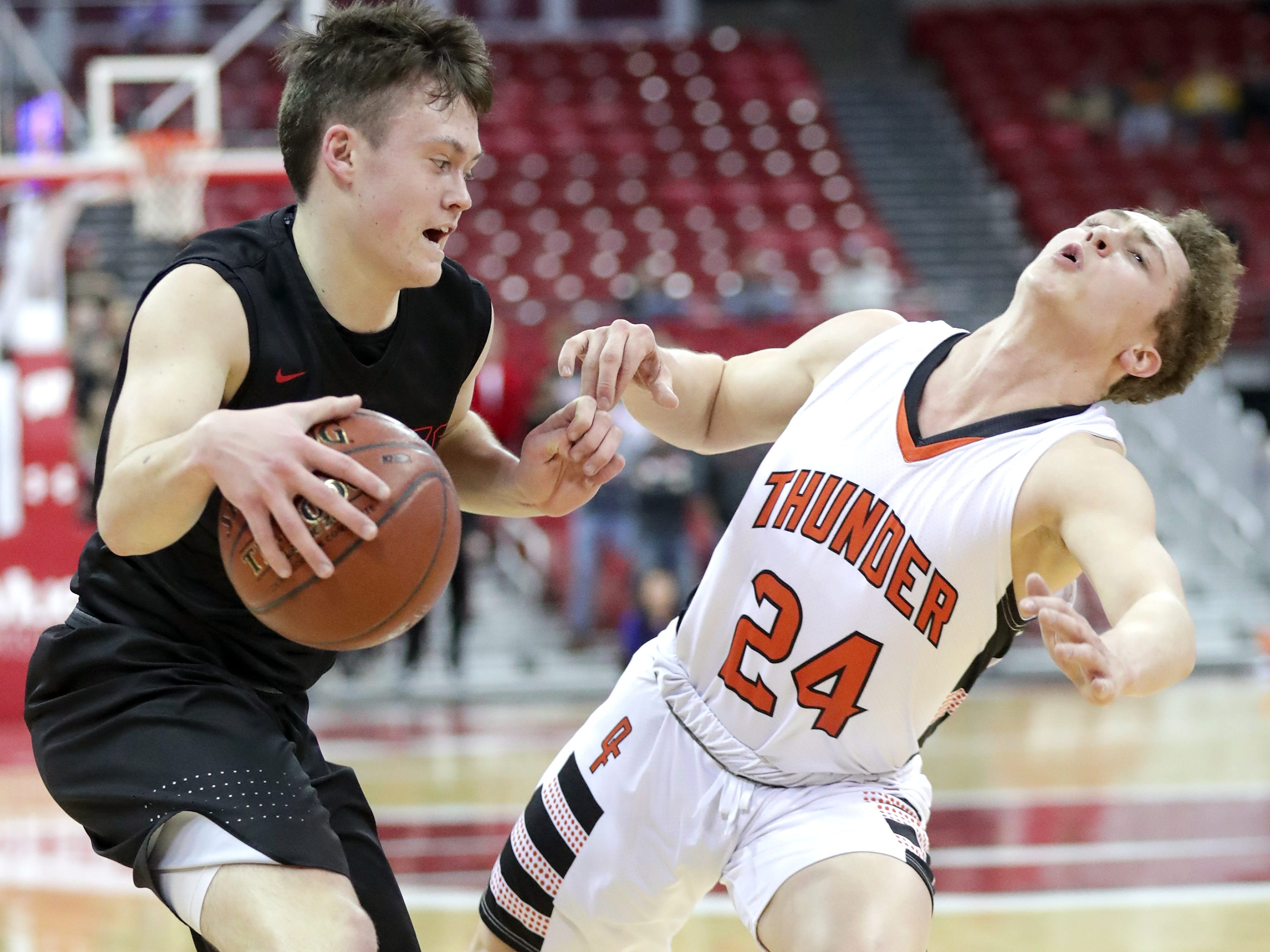 Lourdes Academy's #12 Joshua Bauer drives against Osseo-Fairchild High School's #24 Caden Boettcher during their WIAA Division 4 boys basketball state semifinal on Thursday, March 14, 2019, at the Kohl Center in Madison, Wis.