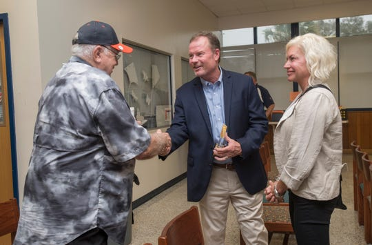 Tracey Durant looks on as her husband and Hall of Fame class of 2018-2019 inductee Joe Durant, center, is congratulated by previous inductee Howard Fletcher at Escambia High School in Pensacola on March 14, 2019.  Fletcher, a 5-time state champion golf coach at Escambia High School, was a member of the 1st Hall of Fame class.