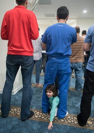 Dr. Danish Ali prays as his son Haris Ali, 2, crawls between his legs during Jumu'ah (Friday Prayer) at the Islamic Center of Northwest Florida in Pensacola on Friday, March 15, 2019.