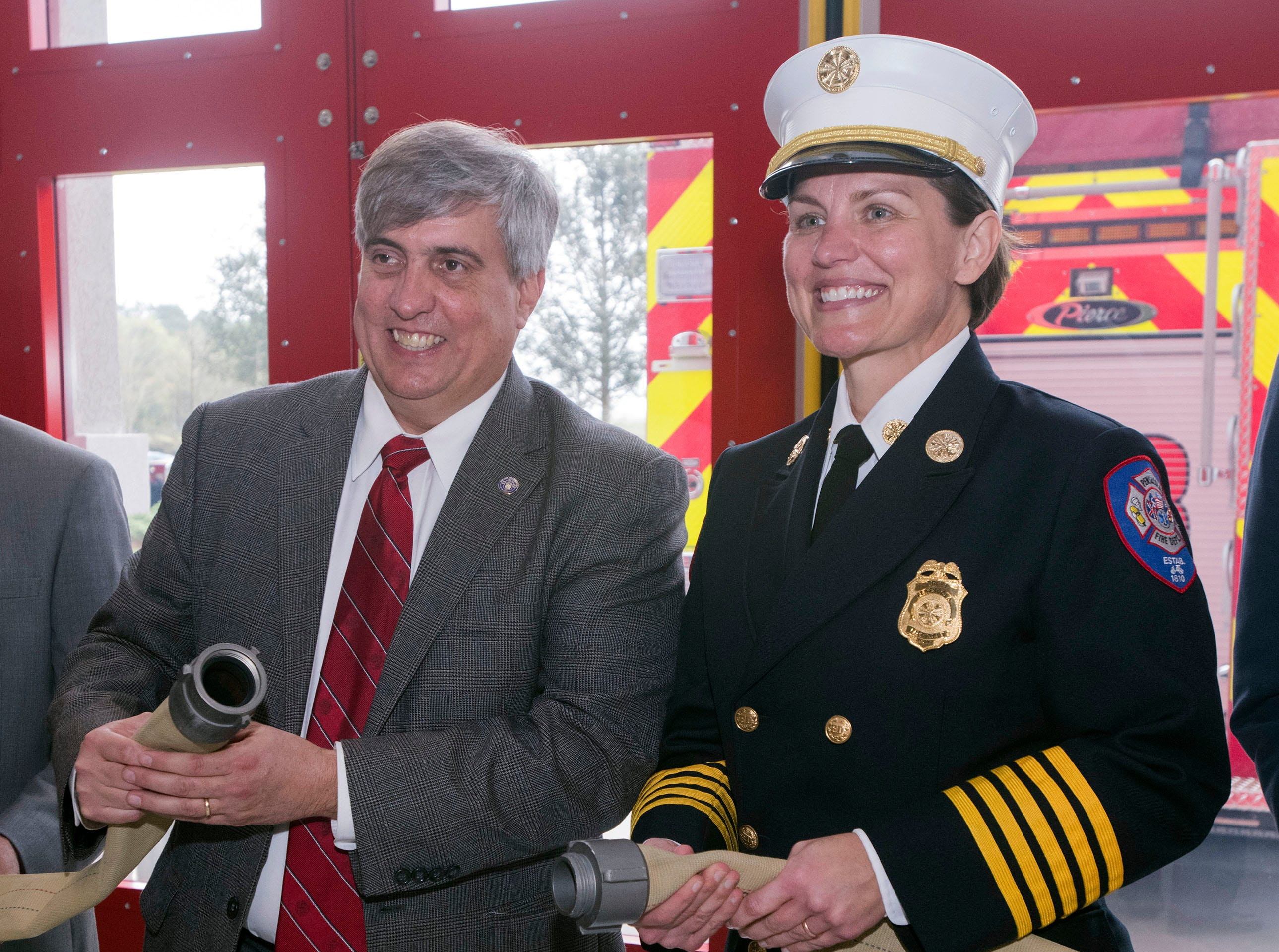 Mayor Grover Robinson and Fire Chief Ginny Cranor take part in the uncoupling of the hose ceremony during a dedication for the new Pensacola Fire Sation Three off Summit Blvd on Thursday, March 14, 2019. The new building, dedicated Thursday, replaces the current station built in 1969 — money from the local option sales tax paid for the project.
