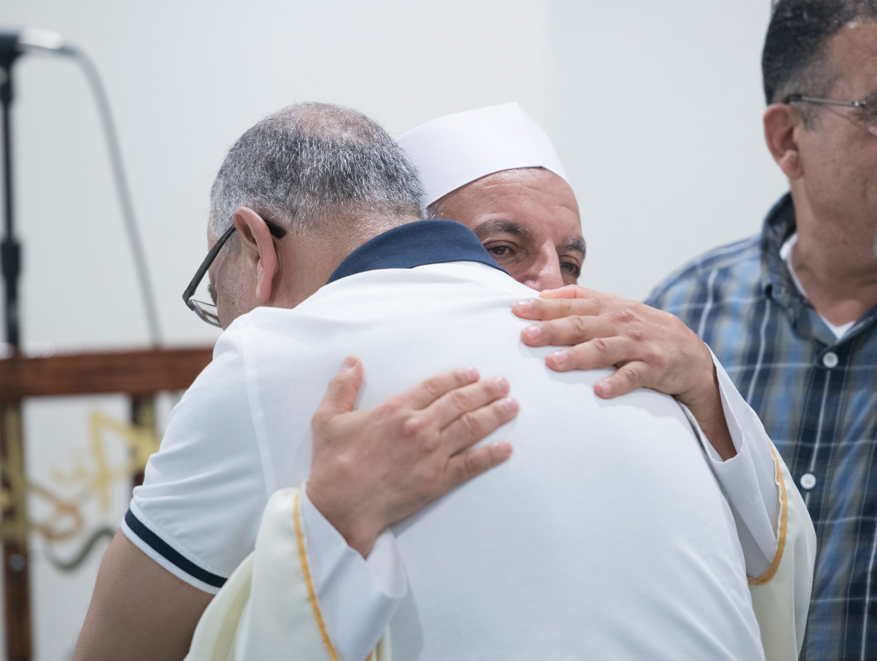 Imam Hosny Ibriham, top, gives a hug during Jumu'ah (Friday Prayer) at the Islamic Center of Northwest Florida in Pensacola on Friday, March 15, 2019.