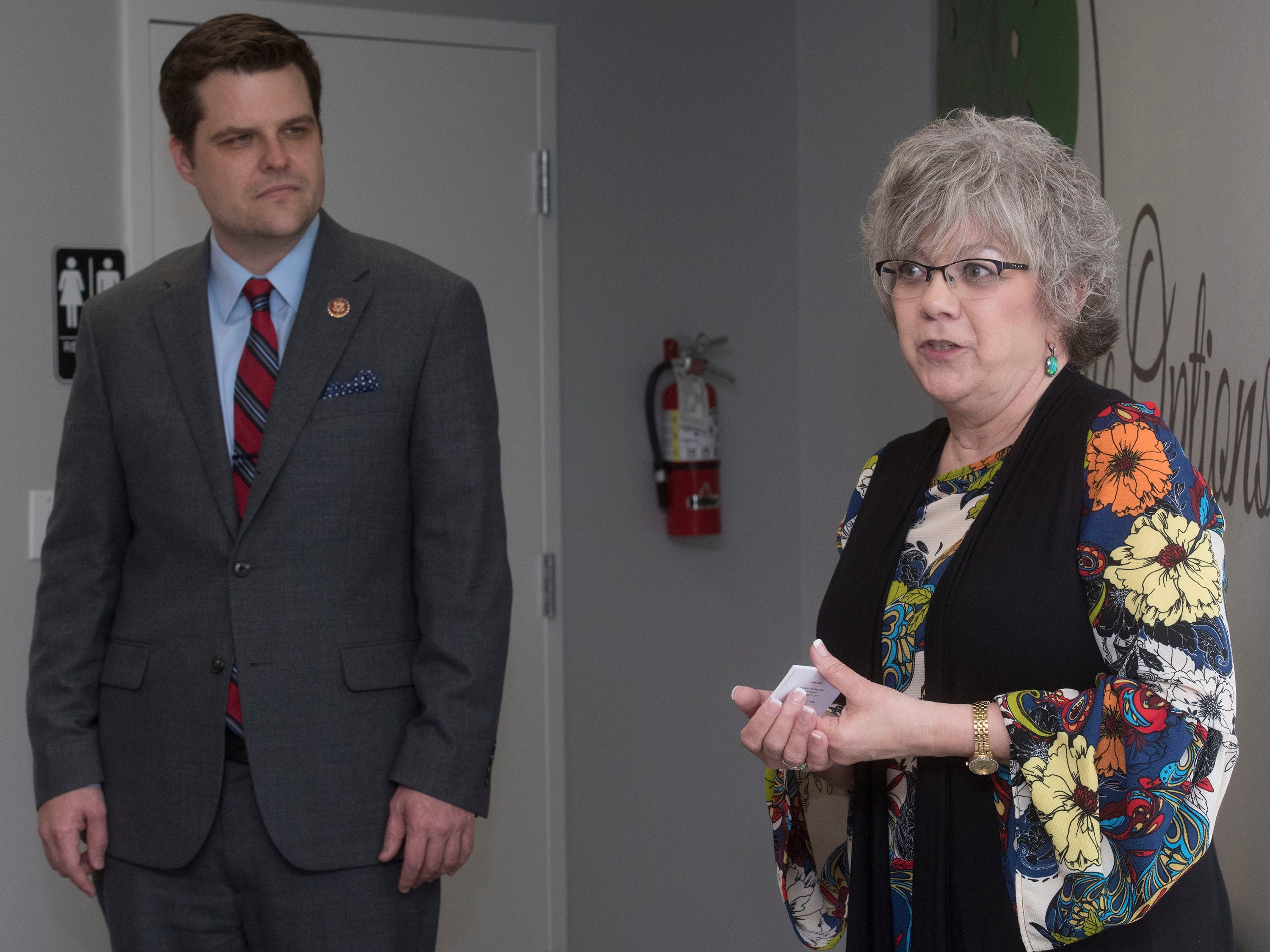 Cindy Roberts, the executive director of Life Options Clinic in Milton, describes the organization's mission, while Congressman Matt Gaetz looks on, during the dedication of the organization's building on Friday, March 15, 2019.