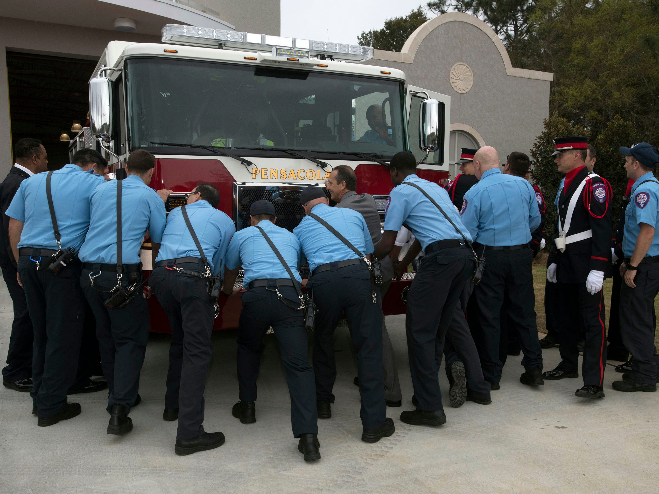 Members of the Pensacola Fire Department push department's newest engine into the new Fire Station Three off Summit Blvd during a dedication of the new firehouse on Thursday, March 14, 2019.