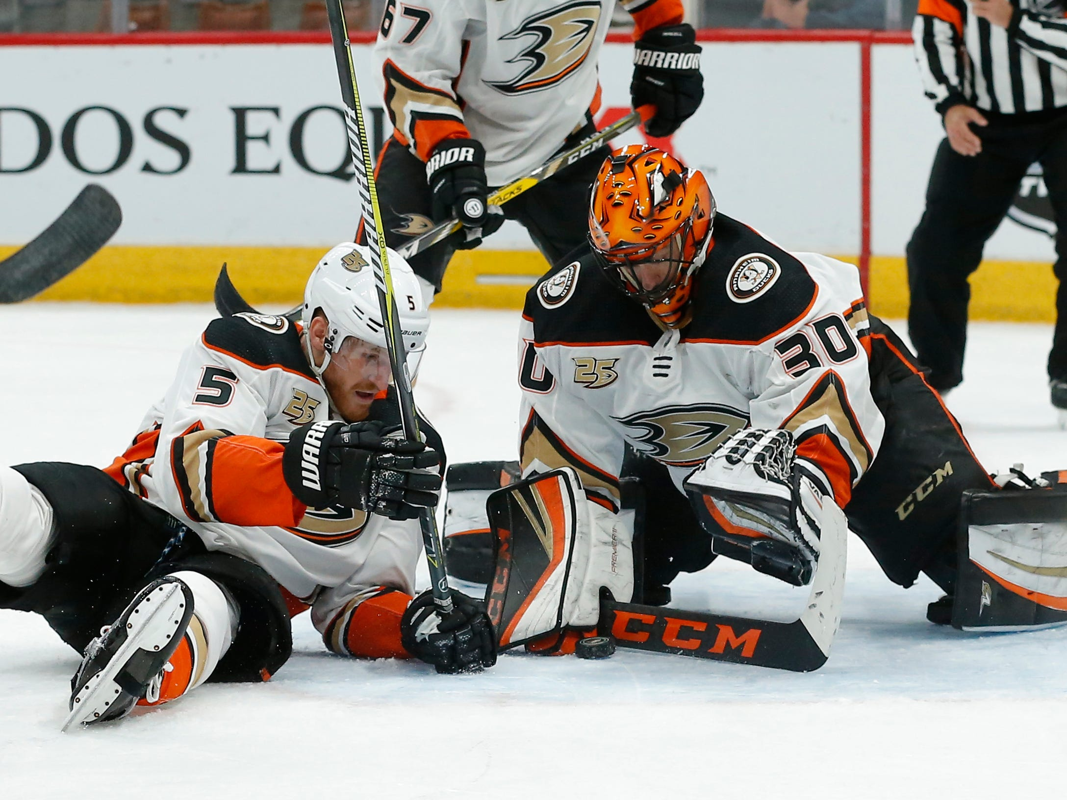 Anaheim Ducks goaltender Ryan Miller (30) and Korbinian Holzer cover up the puck in the second period during an NHL hockey game against the Arizona Coyotes, Thursday, March 14, 2019, in Glendale, Ariz.