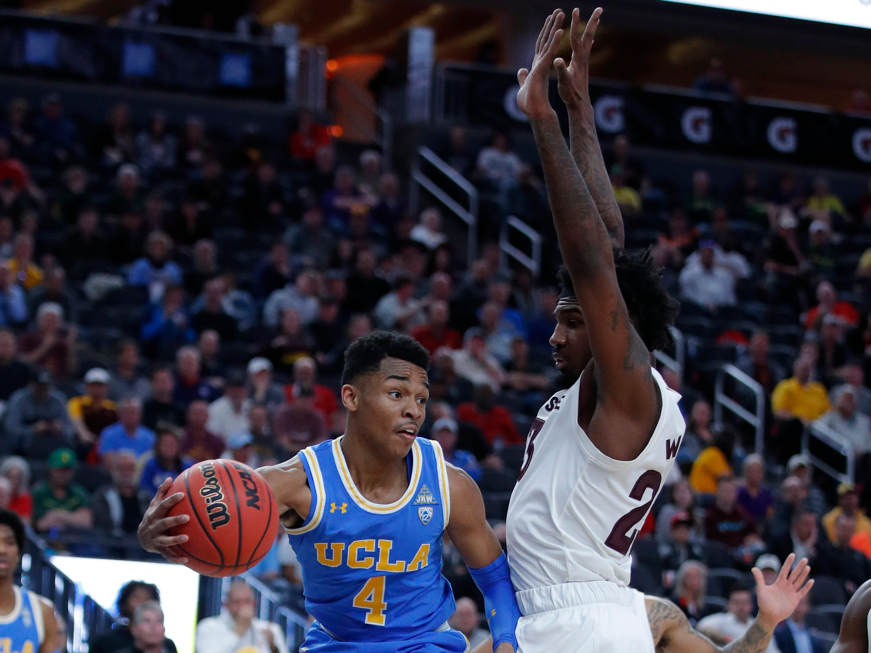 UCLA's Jaylen Hands passes around Arizona State's Romello White during the first half of an NCAA college basketball game in the quarterfinals of the Pac-12 men's tournament Thursday, March 14, 2019, in Las Vegas.