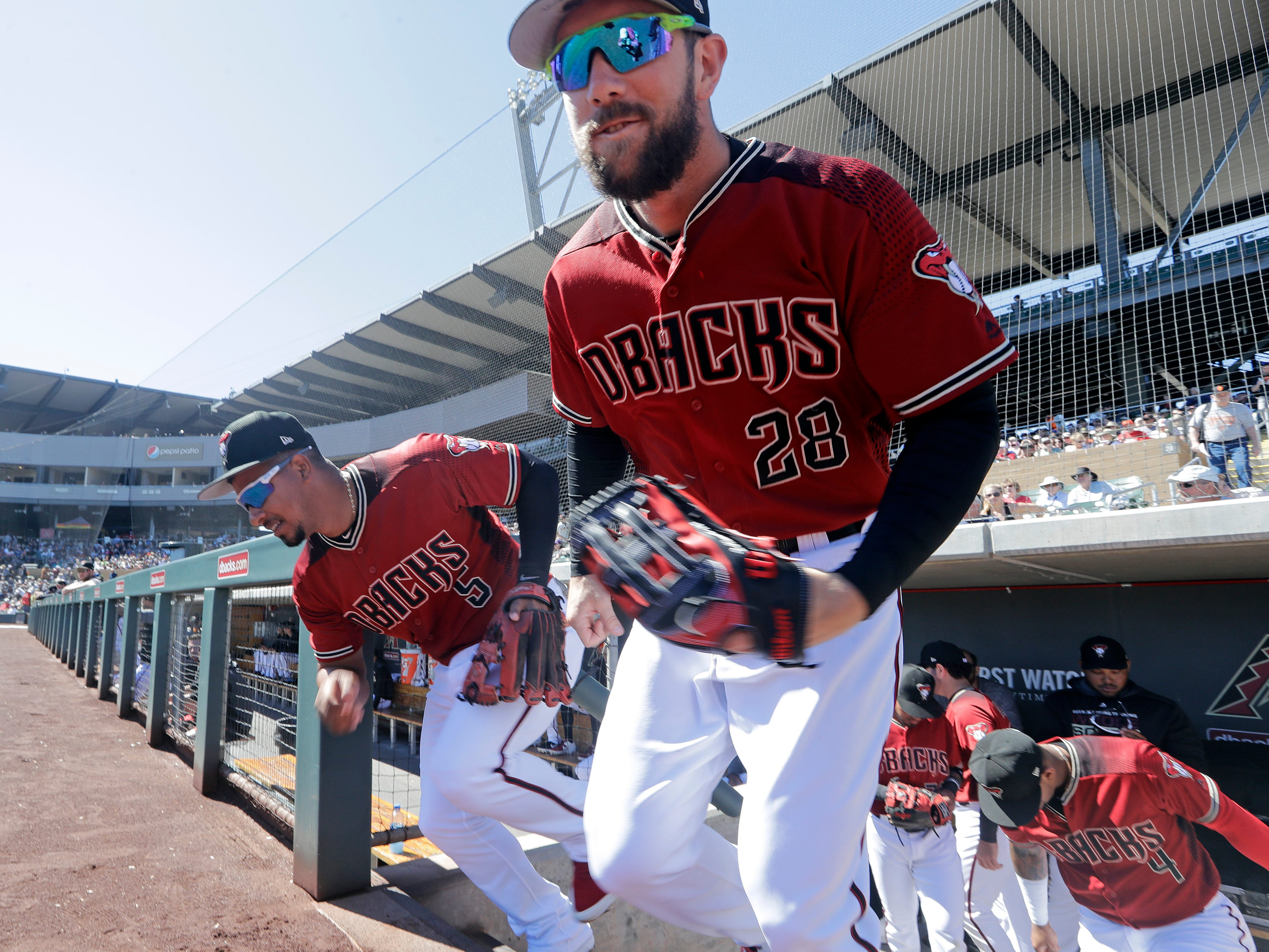 Arizona Diamondbacks' Steven Souza Jr. (28) and Eduardo Escobar (5) lead players out of the dugout before a spring training baseball game against the San Francisco Giants Thursday, March 14, 2019, in Scottsdale, Ariz.