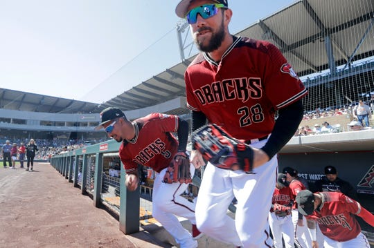 Steven Souza Jr. (28) and Eduardo Escobar (5) lead the Diamondbacks out of the dugout before a spring training camp against the Giants on March 14.