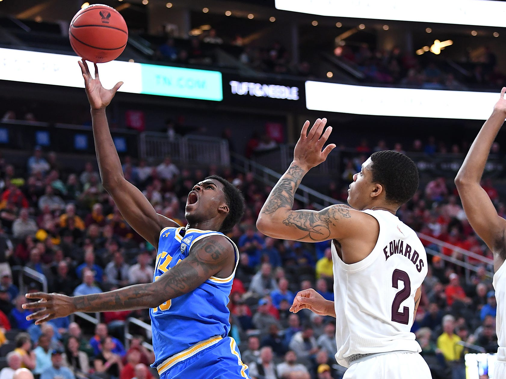 Mar 14, 2019; Las Vegas, NV, United States; UCLA Bruins guard Kris Wilkes (13) shoots inside the defense of Arizona State Sun Devils guard Rob Edwards (2) during the second half of a Pac-12 conference tournament game at T-Mobile Arena.