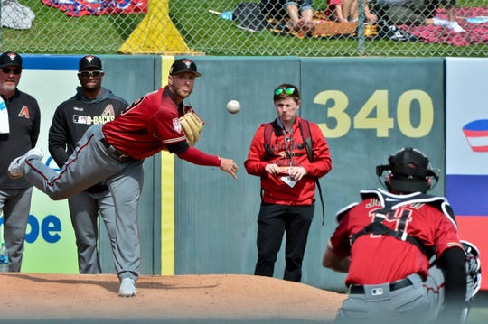 Mar 15, 2019; Tempe, AZ, USA; Arizona Diamondbacks starting pitcher Merrill Kelly (29) warms up in the bullpen with catcher Joseph Caleb (14) prior to the game against the Los Angeles Angels at Tempe Diablo Stadium. Mandatory Credit: Matt Kartozian-USA TODAY Sports
