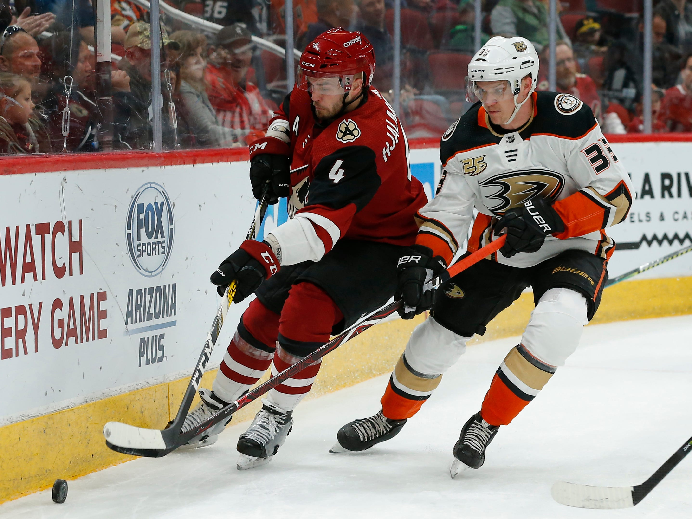 Arizona Coyotes defenseman Niklas Hjalmarsson (4) and Anaheim Ducks right wing Jakob Silfverberg (33) race for the puck in the first period during an NHL hockey game, Thursday, March 14, 2019, in Glendale, Ariz.