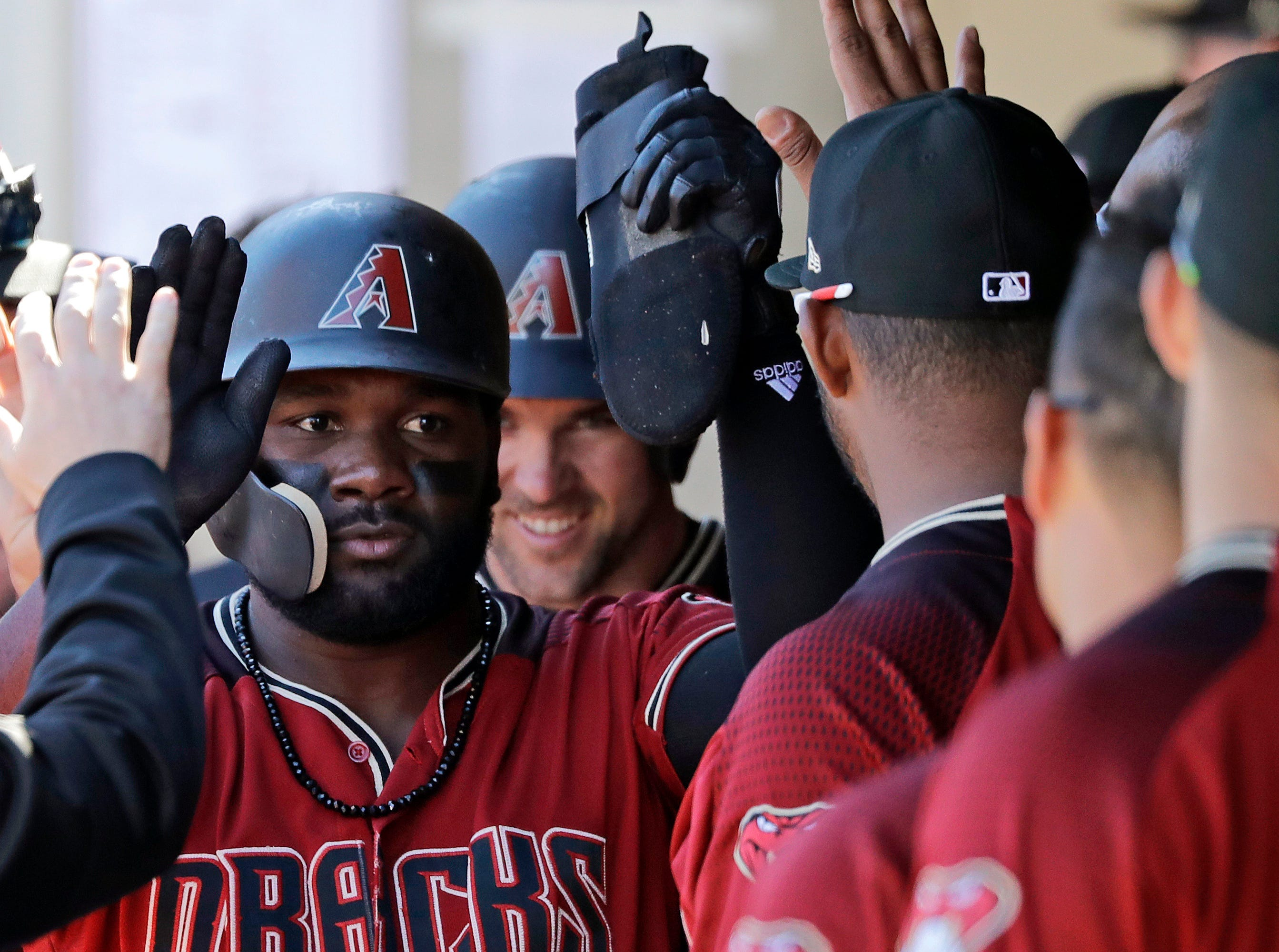 Arizona Diamondbacks' Abraham Almonte, left, is followed by Matt Szczur for congratulations in the dugout after they scored in the seventh inning of a spring training baseball game against the San Francisco Giants, Thursday, March 14, 2019, in Scottsdale, Ariz.