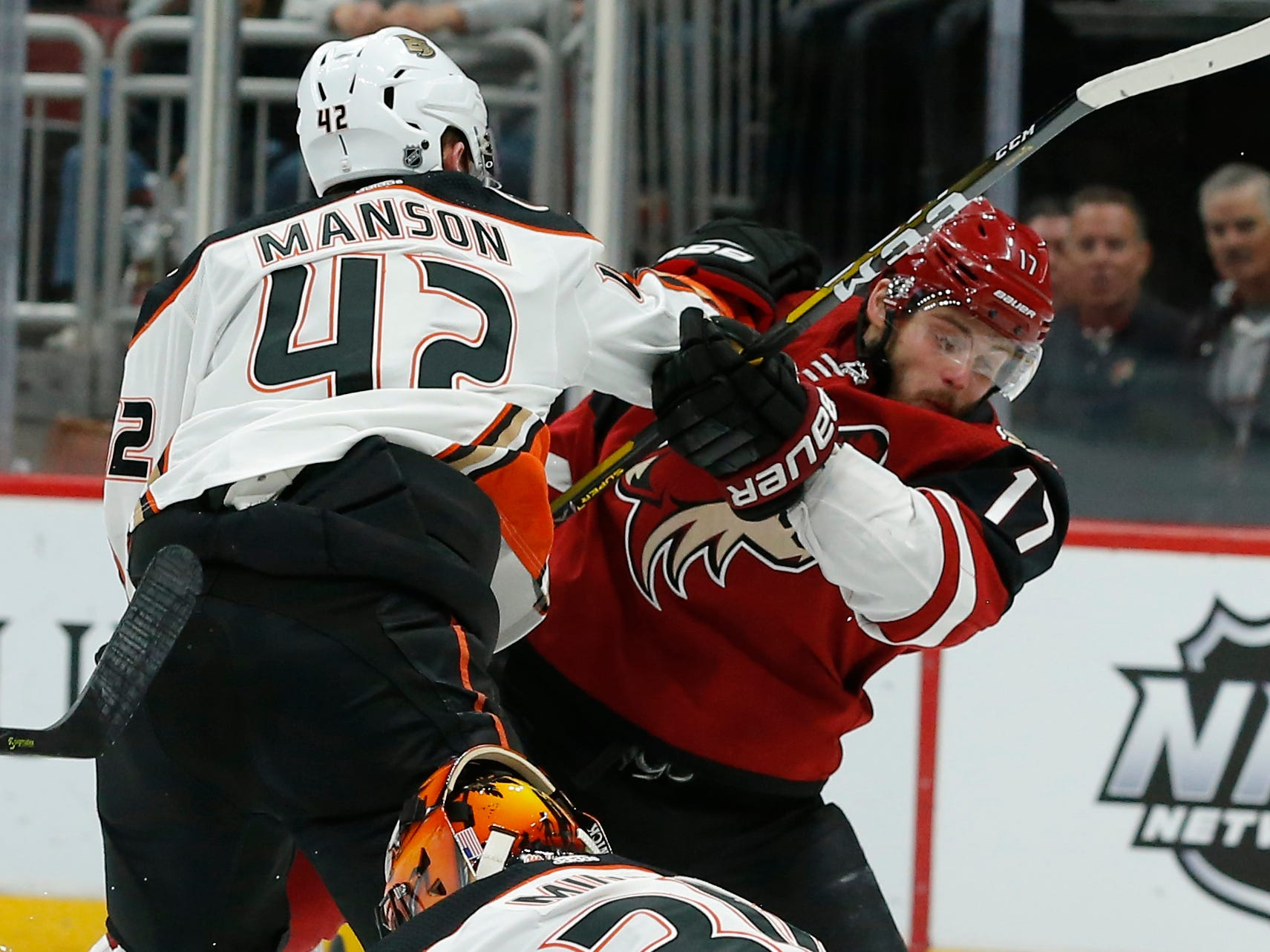 Anaheim Ducks goaltender Ryan Miller (30) covers up the puck as Josh Manson (42) clears Arizona Coyotes center Alex Galchenyuk (17) from the crease during the second period during an NHL hockey game Thursday, March 14, 2019, in Glendale, Ariz.