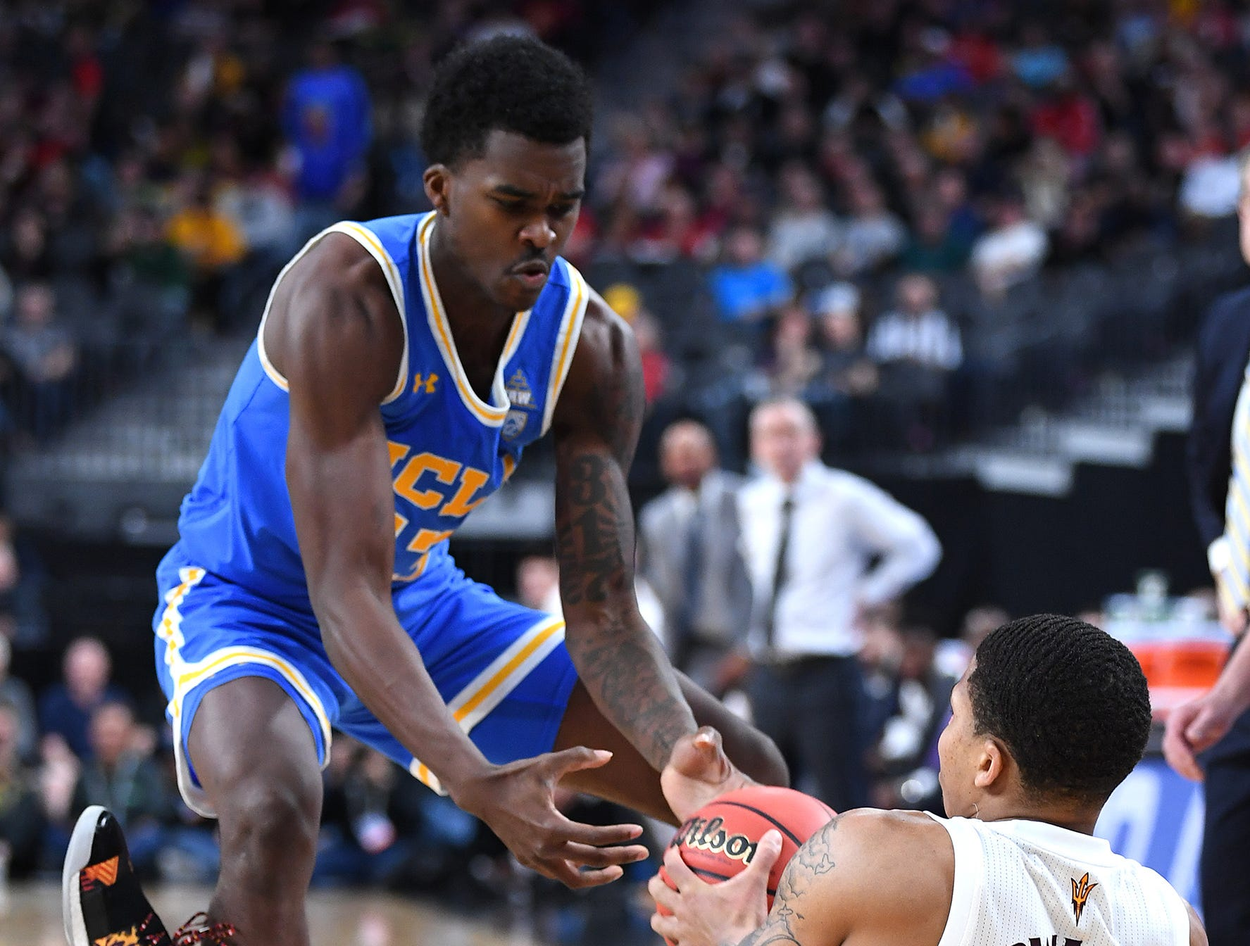 Mar 14, 2019; Las Vegas, NV, United States; UCLA Bruins guard Kris Wilkes (13) looks to steal the ball from Arizona State Sun Devils guard Rob Edwards (2) during the second half of a Pac-12 conference tournament game at T-Mobile Arena.