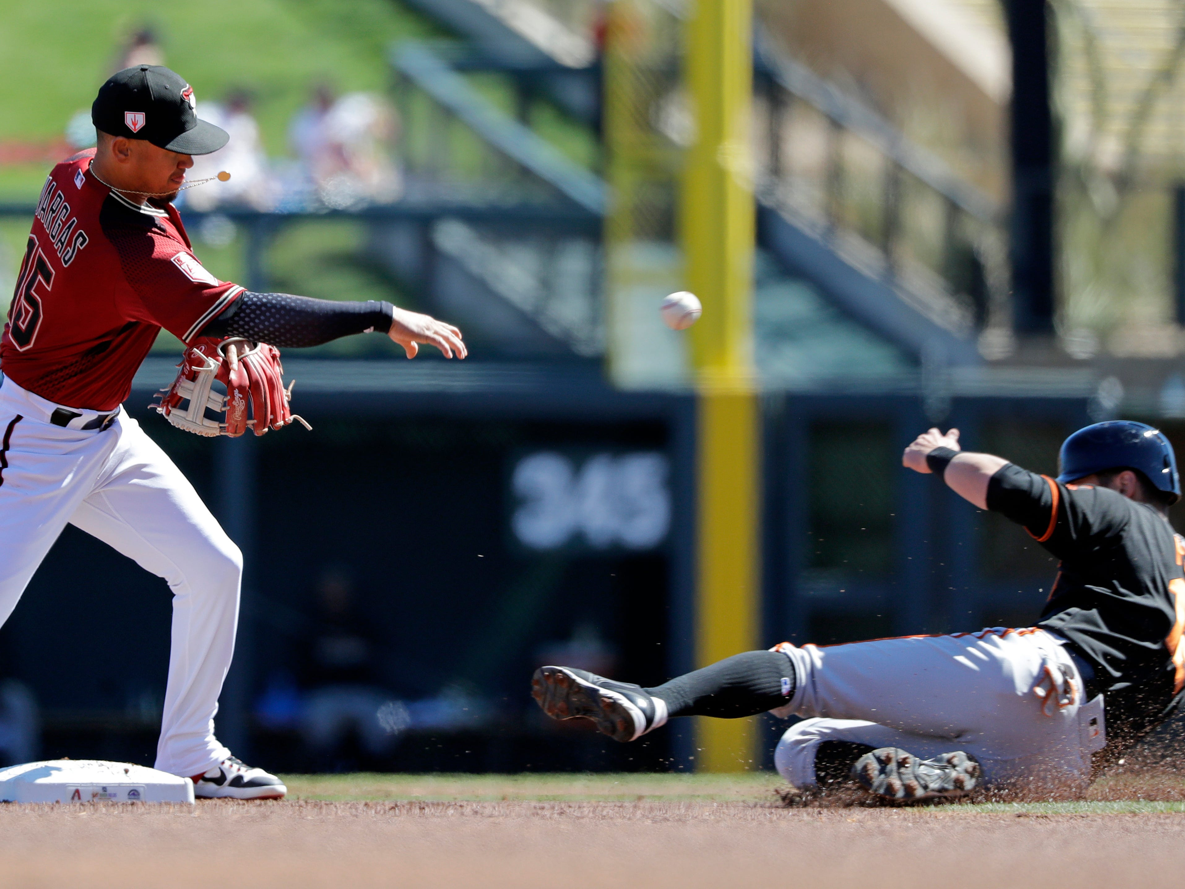Arizona Diamondbacks second baseman Ildemaro Vargas, left, throws to first after forcing out San Francisco Giants' Joe Panik, right, at second in the first inning of a spring training baseball game Thursday, March 14, 2019, in Scottsdale, Ariz. Giants' Buster Posey was out at first base on the double play.