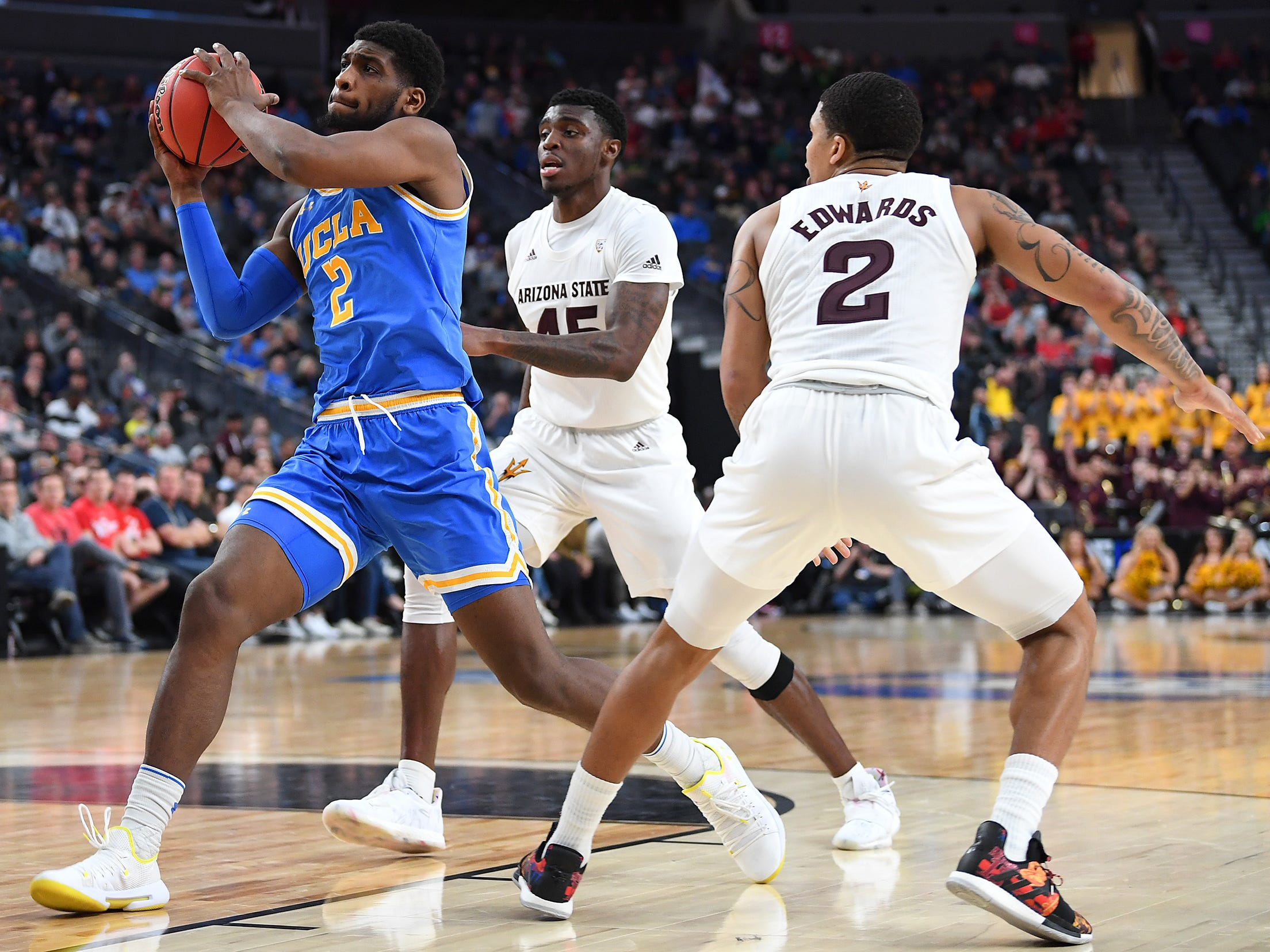 Mar 14, 2019; Las Vegas, NV, United States; UCLA Bruins forward Cody Riley (2) looks to shoot past Arizona State Sun Devils forward Zylan Cheatham (45) and Arizona State Sun Devils guard Rob Edwards (2) during the second half of a Pac-12 conference tournament game at T-Mobile Arena.