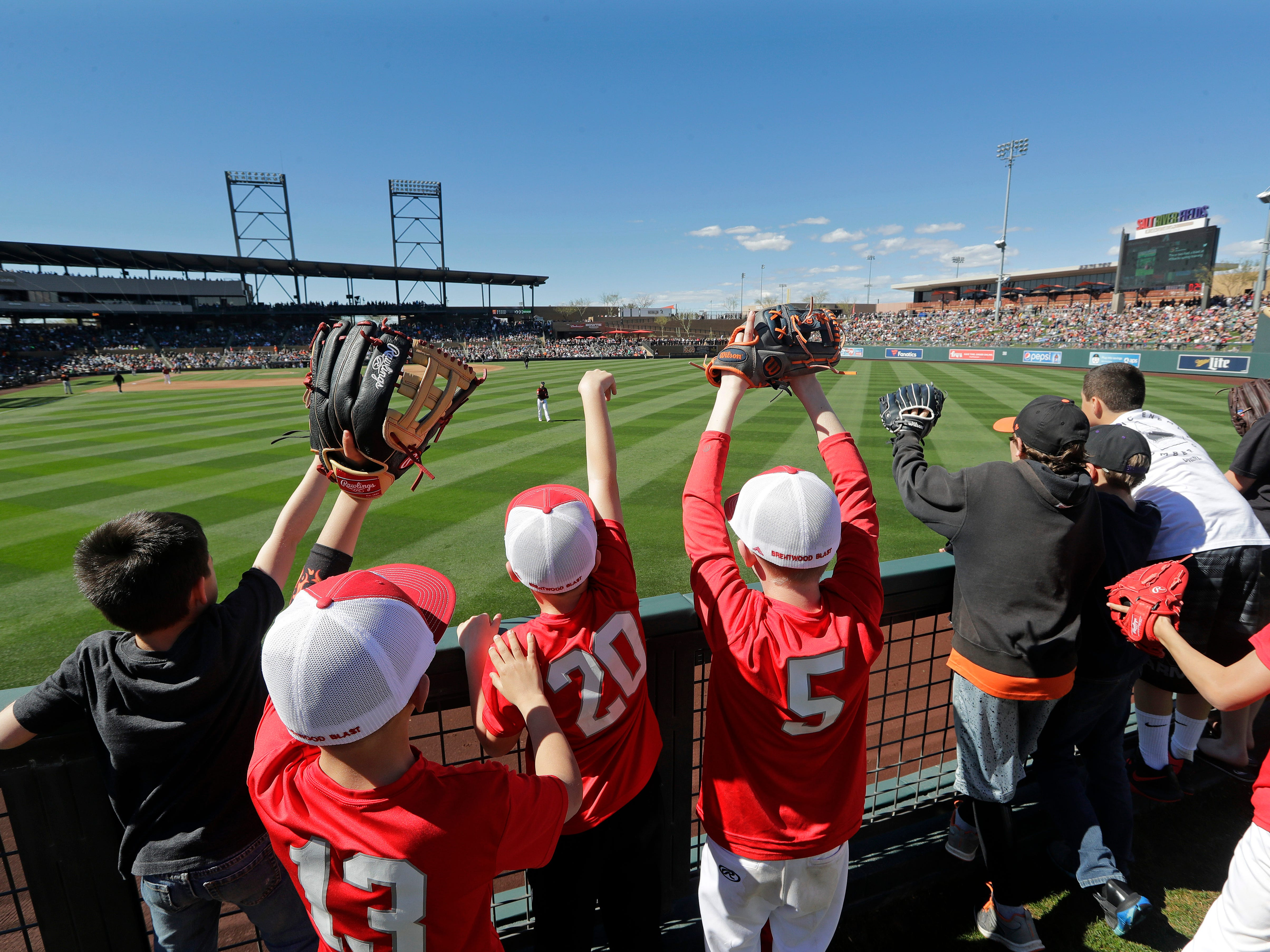 Children line the left field fence as they call for a ball from players warming up between innings of a spring training baseball game between the San Francisco Giants and the Arizona Diamondbacks, Thursday, March 14, 2019, in Scottsdale, Ariz.
