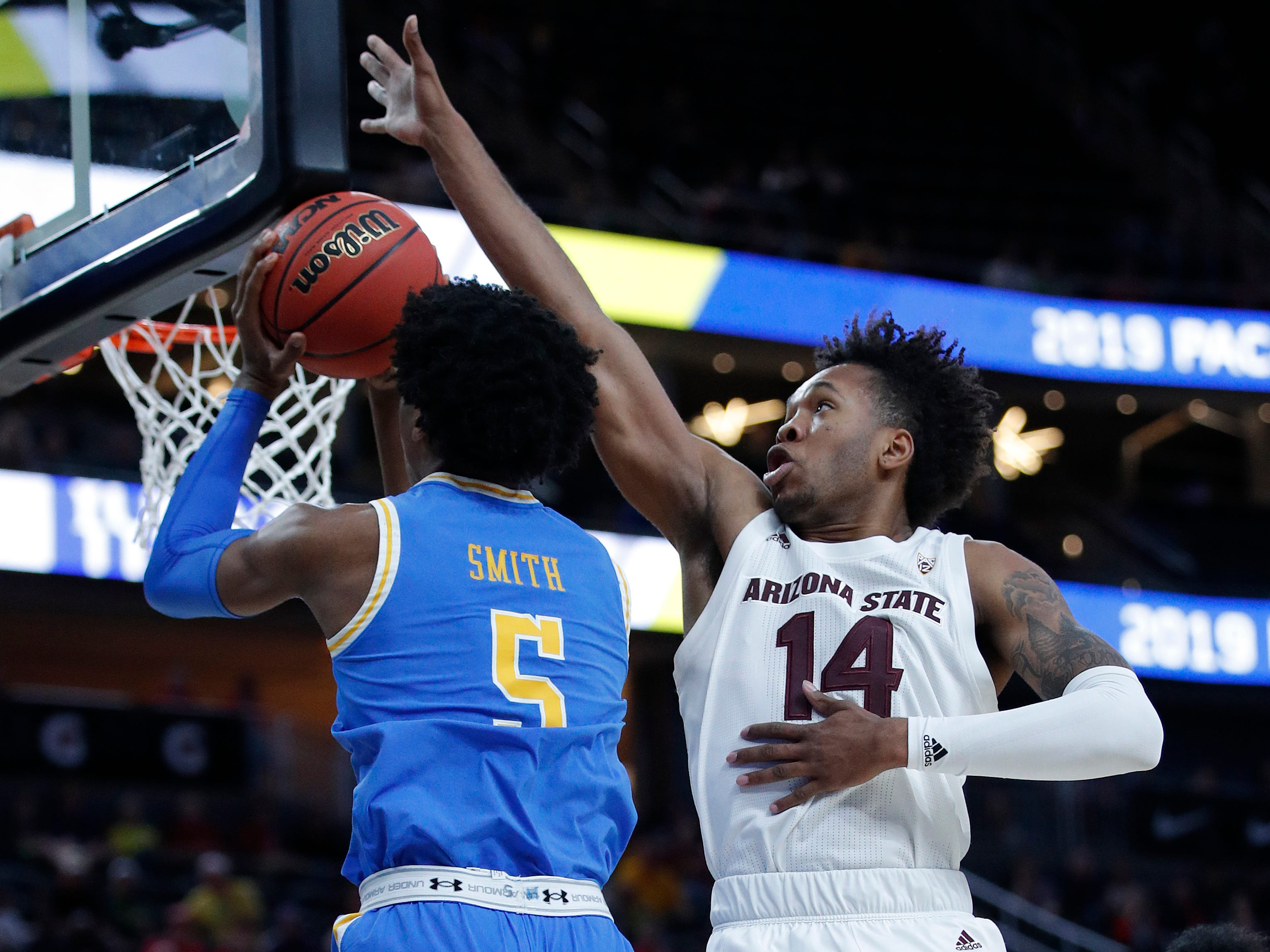 Arizona State's Kimani Lawrence, right, blocks a shot by UCLA's Chris Smith during the first half of an NCAA college basketball game in the quarterfinals of the Pac-12 men's tournament Thursday, March 14, 2019, in Las Vegas.