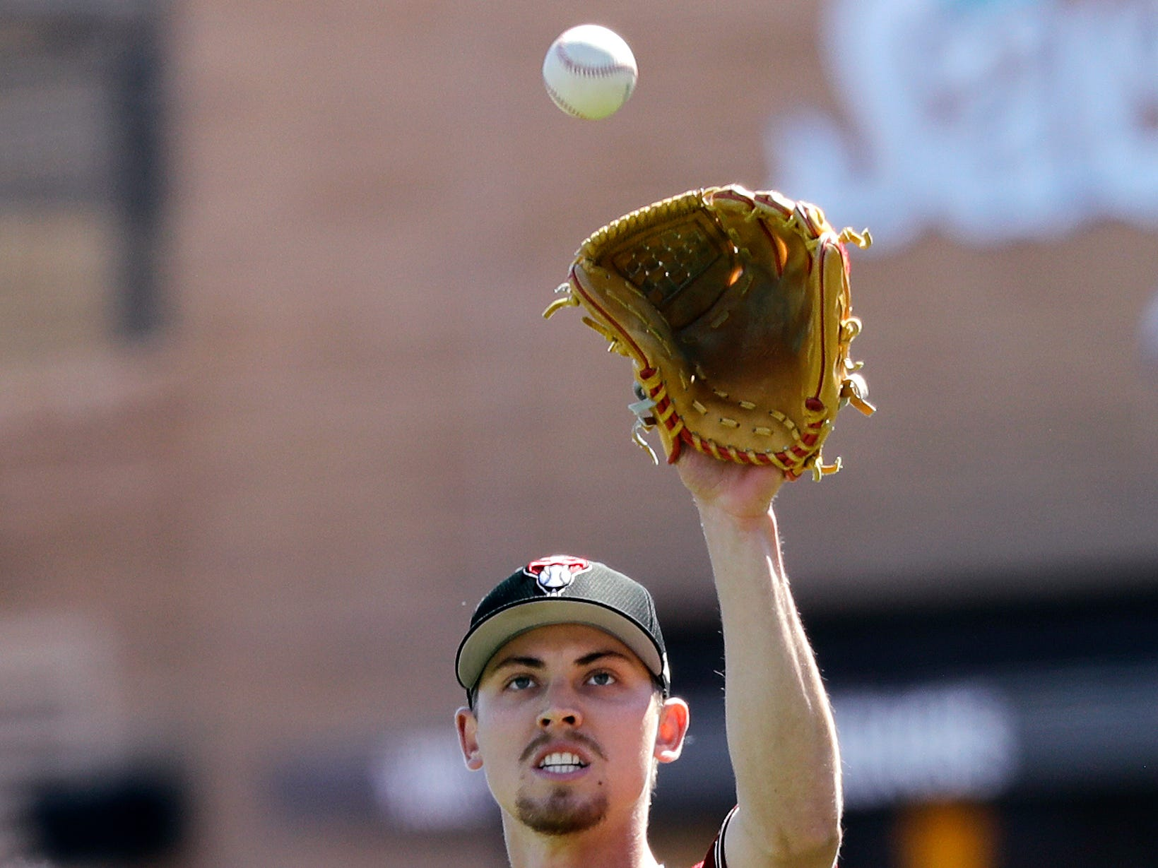 Arizona Diamondbacks starting pitcher Luke Weaver reaches for a ball against the San Francisco Giants in a spring training baseball game Thursday, March 14, 2019, in Scottsdale, Ariz.