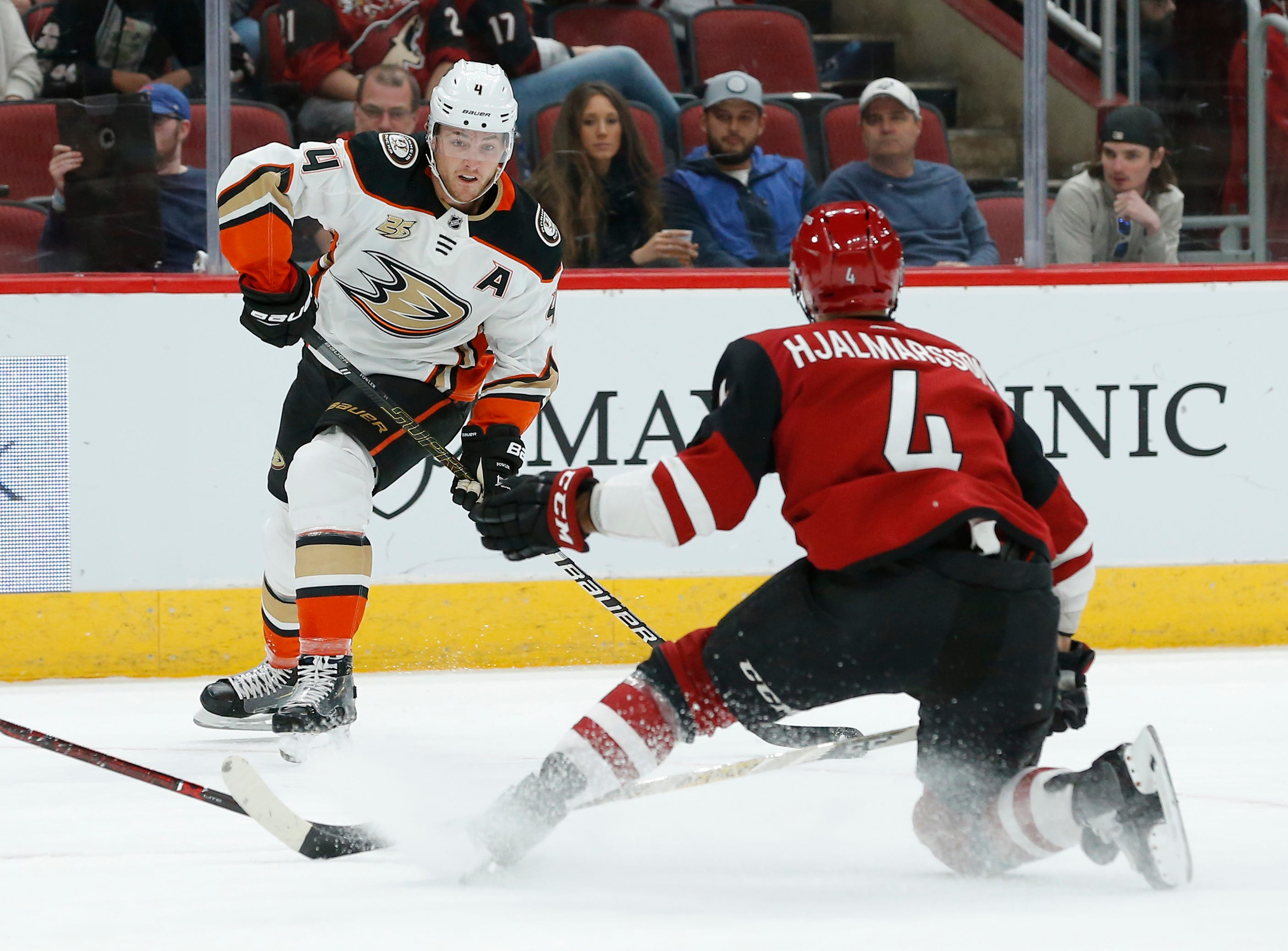 Anaheim Ducks defenseman Cam Fowler (4) shoots in front of Arizona Coyotes defenseman Niklas Hjalmarsson in the first period during an NHL hockey game, Thursday, March 14, 2019, in Glendale, Ariz.