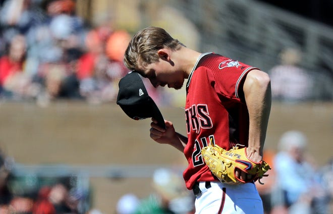 Arizona Diamondbacks starting pitcher Luke Weaver pauses for a few moments before throwing against the San Francisco Giants in the third inning of a spring training baseball game Thursday, March 14, 2019, in Scottsdale, Ariz.