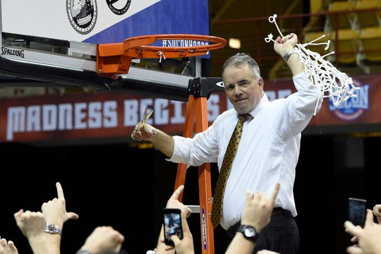Wofford head coach Mike Young raises the basketball net in the air to celebrate his team's 70-58 win over UNC-Greensboro for the Southern Conference tournament championship, Monday, March 11, 2019, in Asheville, N.C.