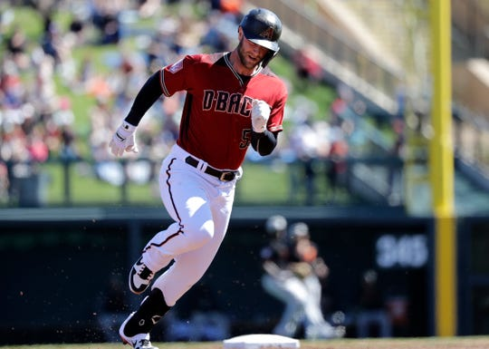 Arizona Diamondbacks' Christian Walker races to third base on his triple against the San Francisco Giants in the second inning of a spring training baseball game Thursday, March 14, 2019, in Scottsdale, Ariz.