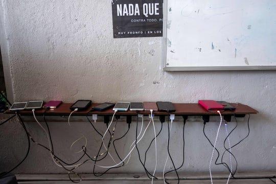 Varios celulares conectados se ven en una mesa, en uno de los refugios de migrantes en Tijuana.